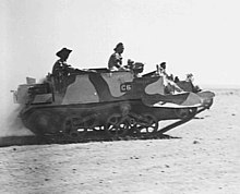 A tracked military vehicle moves across the desert