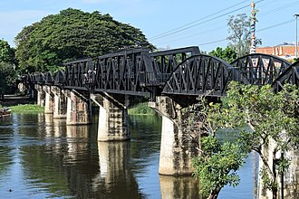 Burma Railway - The railroad bridge over the Mae Klong River (or the Kwai Yai River) in Kanchanaburi Province, Thailand. The span of this bridge is composed of nine curved-truss segments (originals dating back to WWII) and two angular-truss segments (replacements (under war reparations) from Japan after 1945).