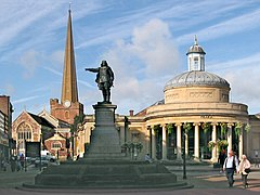 Statue of figure with outstretched arm. To the left a tall church spire and the the right a circular building with columns.