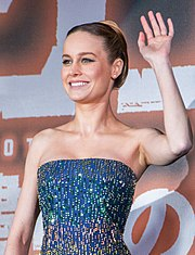 An upper body shot of Brie Larson waving, facing left