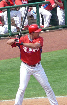 A man in a red baseball jersey and white pinstriped baseball pants holding a black baseball bat over his right shoulder
