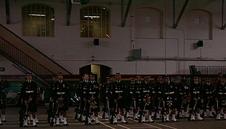 Mewata Armouries - Calgary Highlanders on parade at Mewata Armoury, 2005. The second level of the west side is visible; this entire wing was not part of the additional building and was added later, as were the wooden stairs visible.