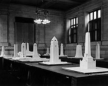 Approximately a dozen monument models sit on tables in a stone walled room.