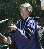 A woman in purple academic regalia passes a diploma to a student, out of frame.