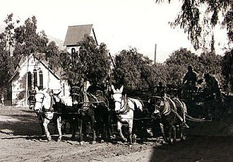 Sierra Madre Boulevard - Central Ave, Sierra Madre CA in 1904, now called Sierra Madre Blvd. A mule team is grading the Ave for the installation of the 1905 Pacific Electric street car, in the background is the Old North Church with the its original barn roof bell tower.