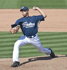 "A man in white pants, a blue baseball jersey with ""PADRES"" in gold on the chest, a blue baseball cap, and a tan baseball glove on his right hand prepares to pitch a baseball with his left hand."
