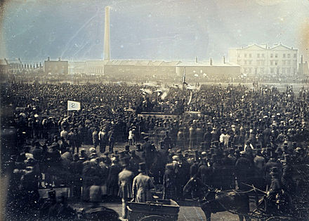 "April 10: ""Monster Rally"" of Chartists held on Kennington Common in London; the first photograph of a crowd depicts it. Chartist meeting, Kennington Common.jpg"