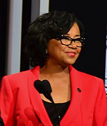 A woman in a red blazer smiles in front of a microphone.