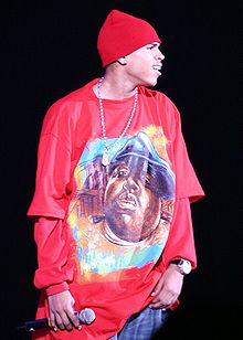 A man in a red hat, wearing a long red t-shirt over a red long-sleeved shirt, holding a microphone in his right hand.