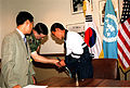 Col. Donald Kropp, United Nations Command Military Armistice Commission (UNCMAC), greets Sgt. Dong In Sop, a North Korean defector, upon his arrival at UNCMAC Headquarters on the Yongsan Army Garrison 990916-A-AX877-001.jpg