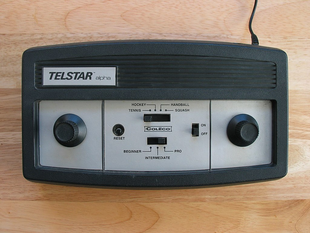 Black and white Telstar video game console on wooden table.