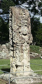 Отдельно стоящий каменный вал с причудливой резьбой, вылепленный в трехмерной форме богато одетой человеческой фигуры, стоящей на открытой лужайке.