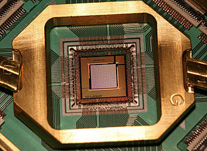"Josephson junction count - Photograph of the D-Wave TwoX ""Washington"" quantum annealing processor chip mounted and wire-bonded in a sample holder. This chip was introduced in 2015 and includes 128,472 Josephson junctions."
