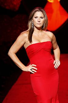 A brunette woman wearing a strapless red dress poses on the end of a fashion runway