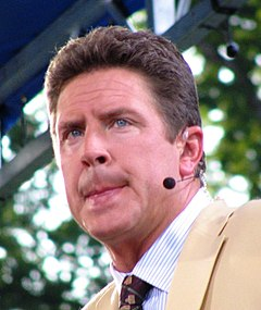 Color head-and-shoulders shot of Marino, in jacket and tie, wearing broadcaster's headset.