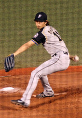 A young Japanese man wearing a grey baseball uniform takes a step forward as he begins to throw a baseball.