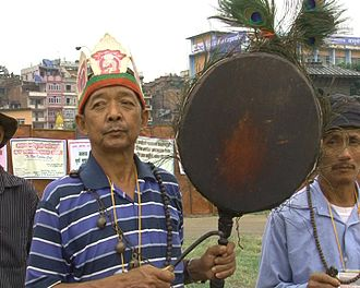 Dhyāngro - A Nepali jhakri holds up a dhyāngro with his left hand, and holds the beater in his right.