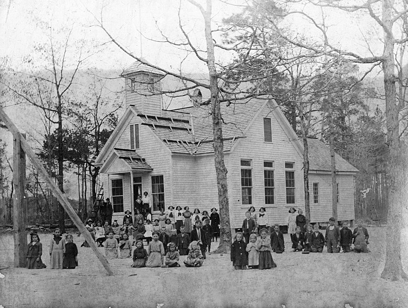 File:Dobbersville School, Wayne County, NC; ca 1900-1905. Students and teachers are posed in a group in front of a large frame school house with a bell cupola on the roof. A handwritten ID label is affixed (18468100554).jpg