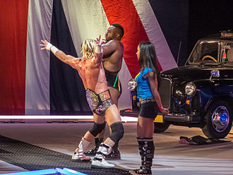 Big E (wrestler) - Big E (back) on Raw in April 2013 with World Heavyweight Champion Dolph Ziggler (center) and their manager AJ Lee (foreground)