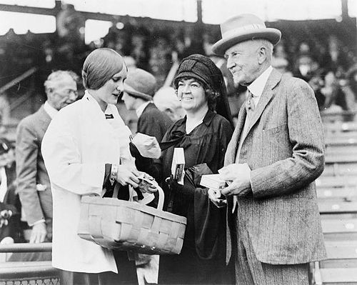 Margaret Speaks, left, daughter of Rep. John C. Speaks of Ohio, photographed while selling peanuts to Edith N. Rogers and Senator Frederick H. Gillett at the game between the Democratic and Republican teams of the House of Representatives.