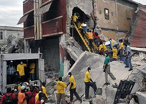 Bucket brigade - A human chain unloads a warehouse after the 2010 Haiti earthquake.