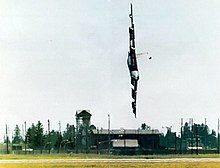 A  B-52 in flight, rolled 90° to the left, very close to the ground and pointing towards it.