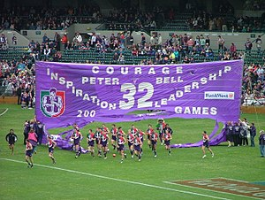 Australian rules football culture - Players running through a banner constructed by supporters.