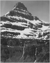 "Full view of snow covered mountain, including area below timberline, ""In Glacier National Park,"" Montana. (Vertical Orie - NARA - 519872.tif"