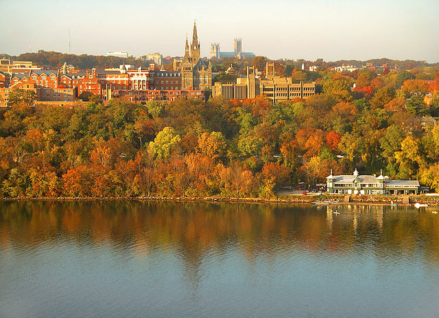 """Georgetown University's main campus taken from the top floor of the Key Bridge Marriott. Washington National Cathedral is visible above campus, and the Washington Canoe Club is in the lower right, on the Potomac River."""