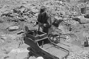 Rocker box - Gold prospector pouring water through his rocker box, Pinos Altos, New Mexico (1940).