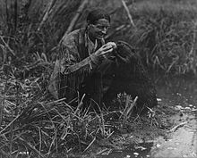 A crouching man in buckskins feeds a roll to a standing beaver.