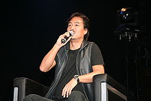 A man sitting in a chair and speaking in a microphone