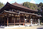 Wooden building with slightly raised floor, an open veranda and a pyramid shaped roof.