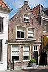 foto van Huis met gepleisterd topgeveltje, boven gedichte pui