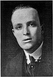 head and shoulders photograph of youngish balding man