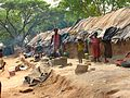 Hyderabad slum dwellers outside mud houses