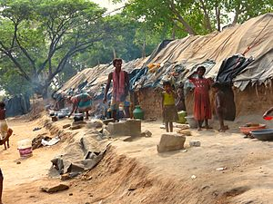 Hyderabad slum dwellers outside mud houses