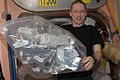ISS-21 Frank De Winne holds a stowage bag containing various beverages in the Unity node.jpg