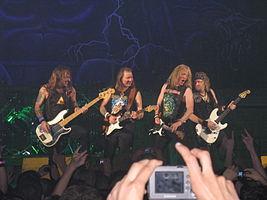 Iron Maiden dum koncerto.Maldekstre dekstren: Steve Harris, Dave Murray, Janick Gers kaj Adrian Smith.