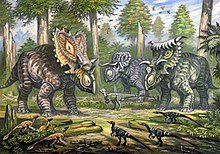 Three large horned dinosaurs in a forest, with small feathered dinosaurs in the foreground