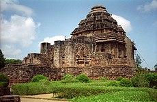 Bildo de kvarangula ŝtontemplo, kun rektaj muroj kaj konusa brustĉemizo. Antaŭ la templo, ŝtonstrukturoj vidiĝas, same kiel verda ĝardeno.