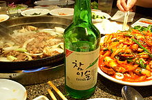 Green bottle on a table with food