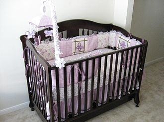 Infant bed - An infant bed with raised mattress, mobile and now-discouraged traditional crib bumpers