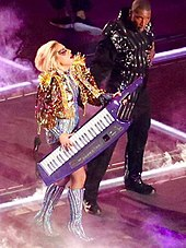 Lady Gaga playing a keytar while wearing a gold jacket.