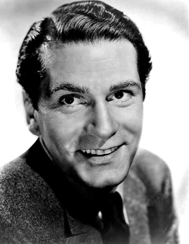Black and white portrait of Laurence Olivier in 1939—a handsome white man with a square face with dark eyes and dark hair, with a split chin and white smile, wearing a suit, around 30 years of age.