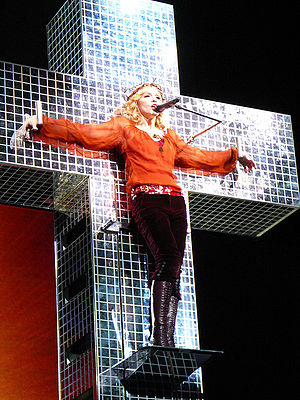 "True Blue (Madonna album) - Madonna wearing a crown of thorns performs the album's first single ""Live to Tell"" while hanging on a mirrored cross, in her 2006 Confessions Tour."