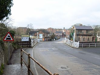 Bedale - Looking into Bedale town from Aiskew across the level crossing. Bedale signal box is on the right and the bridge across Bedale Beck is just beyond the building centre left. The roadsign indicating a level crossing is incorrect - the barriers are clearly there!