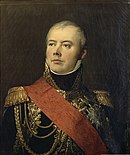 Portrait of a slightly balding man taking an heroic pose with his head tilted back. He wears a dark blue marshal's uniform with elaborate gold braid and a large red sash across his right shoulder.