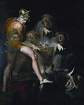 Macbeth, barefoot and wearing body paint or armour and short trousers reaches into an iron pot with three old men in it. They are looking at Macbeth and pointing fingers a figure below.