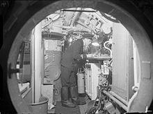 A picture, taken through a round hatchway, shows a machinery filled compartment. A single man, wearing a dark uniform, is bending over a table, lit by a desk-light.